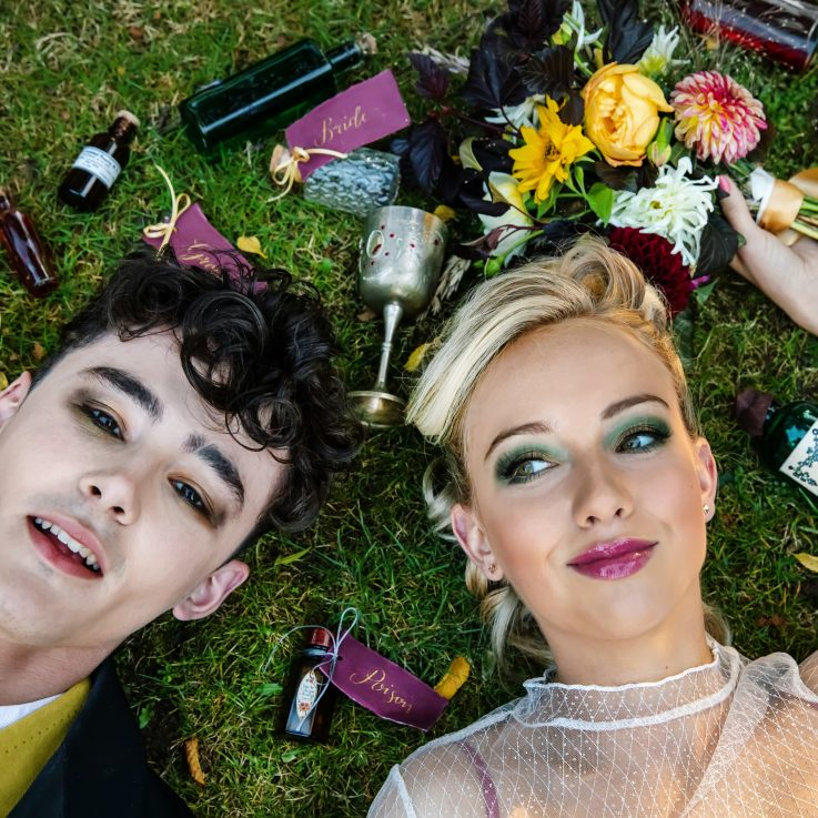 Romeo and Juliet lying in the grass surrounded by goblets flowers and ribbons